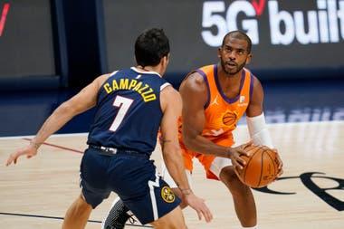 El jugador de los Suns de Phoenix Chris Paul (derecha) se prepara para un lanzamiento ante su rival de los Nuggets de Denver Facundo Campazzo, en la primera mitad del juego de la NBA que enfrentó a ambos equipos, el 1 de enero de 2021, en Denver.