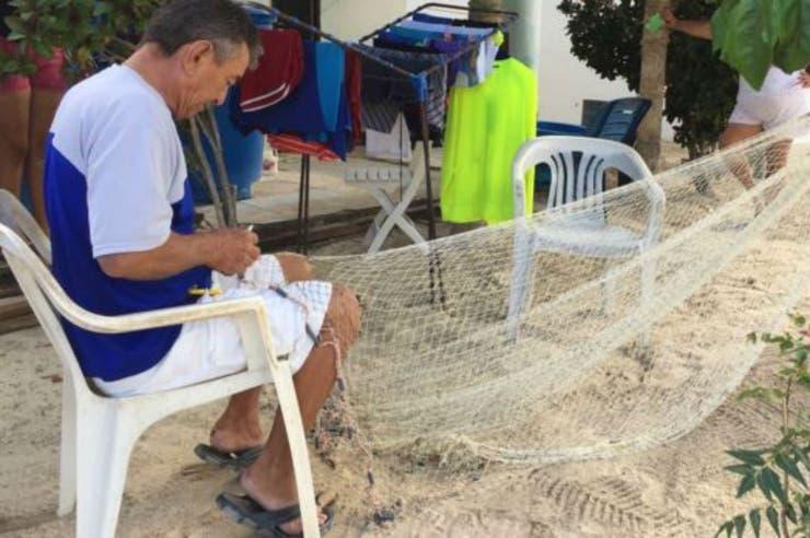 Miguel Salazar repara su atarraya con paciencia a la espera de poder volver a salir a faenar