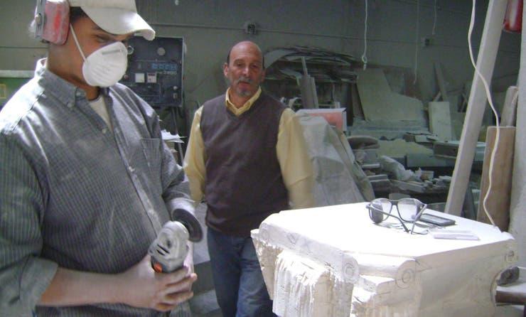 Baccarelli y un oficial confeccionan una pila bautismal en mármol travertino