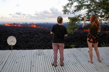 Dos jóvenes tomas fotos del paso de la lava desde el techo de su casa