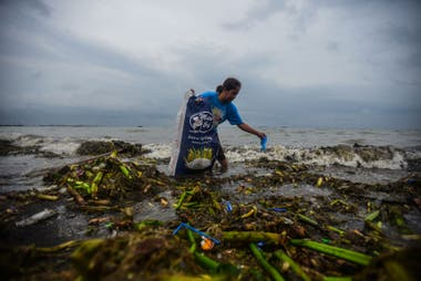 Un joven junta basura del mar en Manila, Filipinas