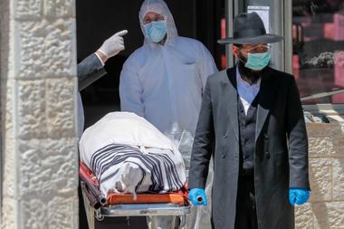 Un rabino israelí camina junto al cadáver, el exrabino sefardí de Israel Eliahu Bakshi-Doron, quien murió por complicaciones por coronavirus