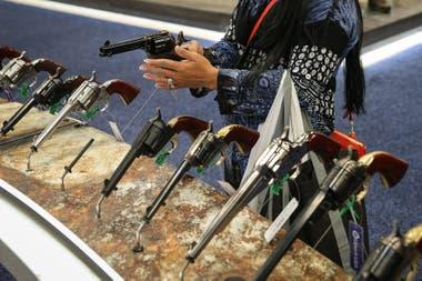 Una mujer inspecciona un revolver en un evento de la NRA llevado a cabo en 2018 en Dallas, Texas