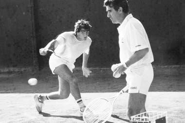 Guillermo Pérez Roldán pega un revés, bajo la mirada de Raúl, durante una pretemporada en Tandil en los 80.