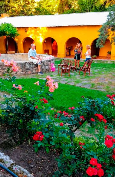 Los anfitriones conversando con una huésped en el florido jardín de La Niña Paula.