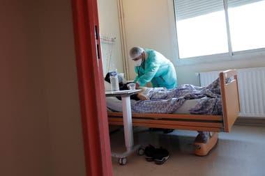 Un médico con máscara y traje de protección, trabaja en una unidad de medicina en el hospital privado Clinique de lEstree - ELSAN en Stain dónde atiende pacientes con coronavirus