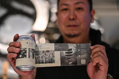 Esta foto tomada el 20 de noviembre de 2020 muestra a Wang Fan, fundador de la Cervecería No.18, posando con una de sus cervezas con imágenes de la lucha de la ciudad contra el coronavirus en Wuhan, provincia central de Hubei en China