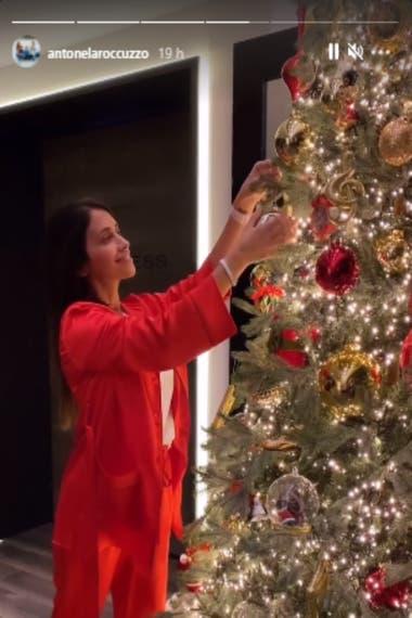 En pijama rojo, a tono con los colores navideños, Roccuzzo ultimó los detalles del imponente árbol de Navidad