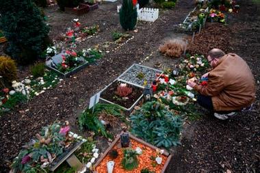 Un visitante enciende una vela en la tumba de su mascota