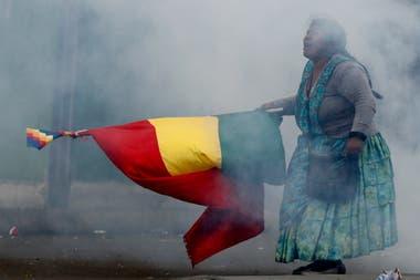 Una seguidora de Evo Morales camina por la calle mientras agita una bandera bolivana