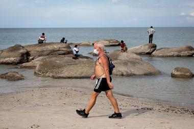 Un hombre con una máscara facial, en medio de la preocupación por la propagación del coronavirus, camina por la playa de Hua Hin en Tailandia el 19 de mayo de 2020