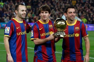 Messi, arropado por Iniesta y Xavi, los cracks que lo rodearon en la época de oro. Aquí, con el Balón de Oro que ganó por su rendimiento en 2011