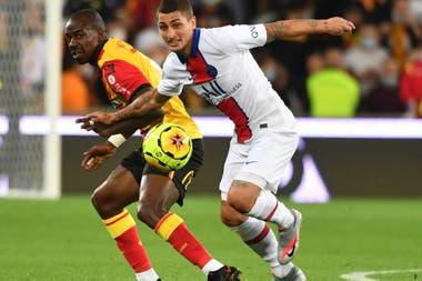 El italiano Marco Verratti, de PSG, intenta llevarse la pelota ante la marca de un rival de Lens. Los campeones de Francia perdieron en el debut por 1 a 0.